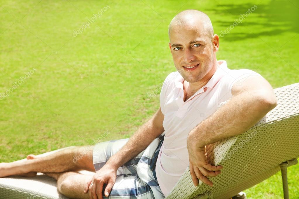 Adult man in casual clothing sitting in a deck chair on a flowery meadow and a rest
