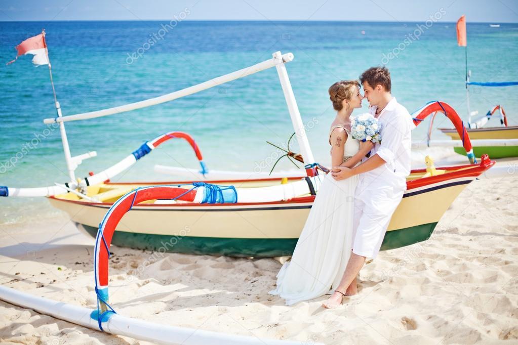 Couple on a beach near the boat