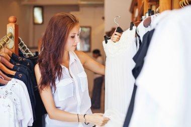 Woman putting a dress to shelve