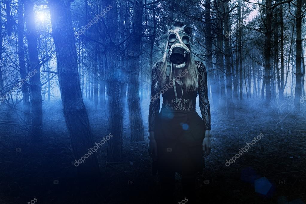 Woman in gas mask with snake in the forest