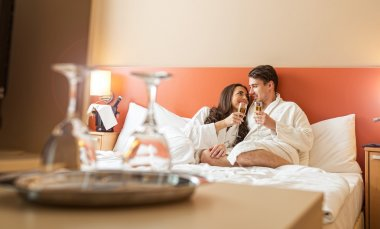 Couple with champagne glasses in bed