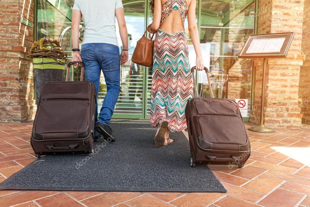 Young couple standing at hotel corridor upon arrival, looking for room, holding suitcases