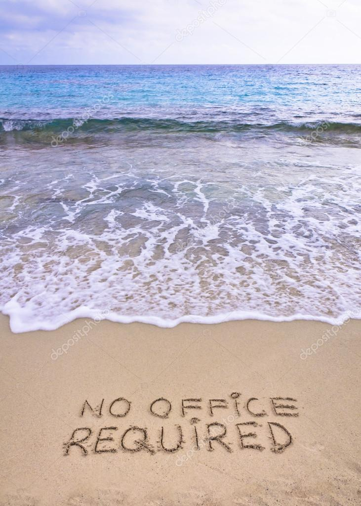No office required written on sand, blue ocean water in background