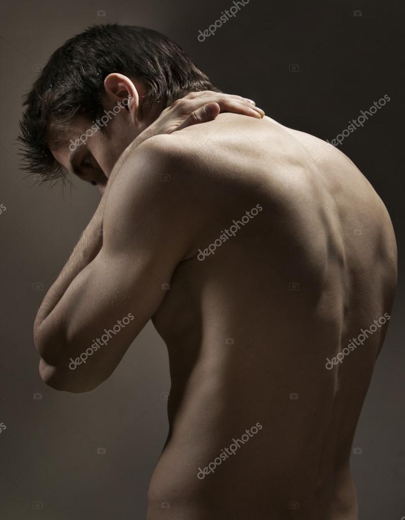 Strong athletic mans back on dark background