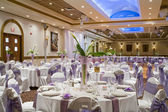 Indoor wedding reception hall with round tables and floral cent