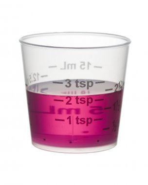 Cold or cough syrup medicine in a measuring cup isolated on whit