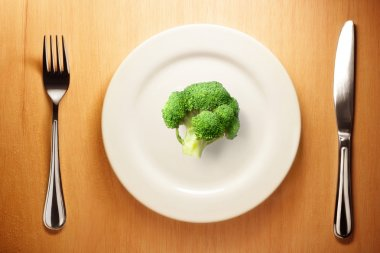 Photo of the fork and knife with white plate and broccoli on woo