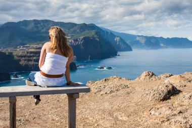 Woman sitting on a bench overlooking Oregon coast and Cannon Beach
