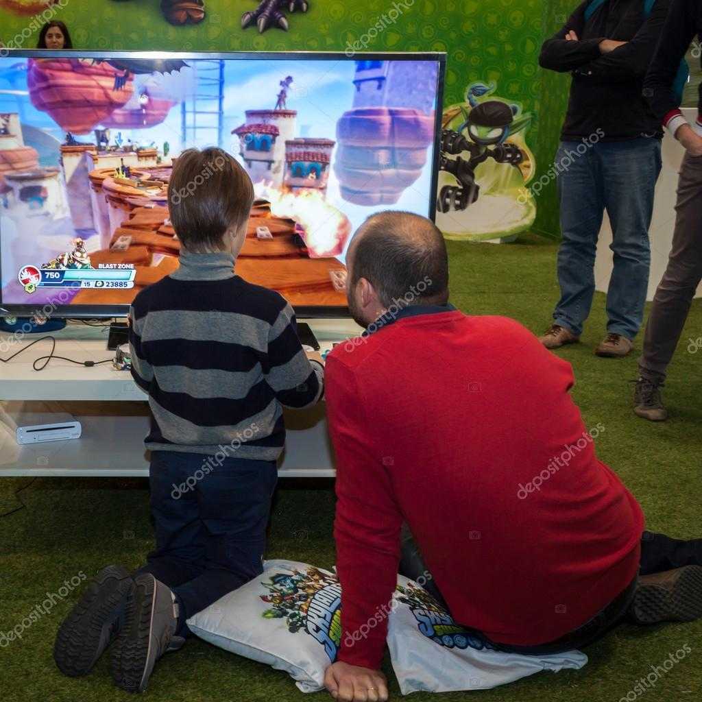 Father and son playing video games at G! come giocare in Milan, Italy