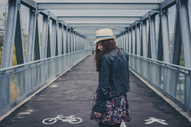 Pretty girl walking away on a bridge