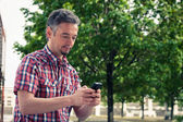 Man in short sleeve shirt texting on phone