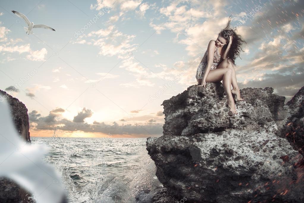 jonge vrouw zittend op een rots en kijken naar de