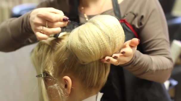 Footage of barber making a hairstyle on womans had