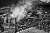 Fotografia un tetto di casa di montagna in bianco e nero con camino fumare