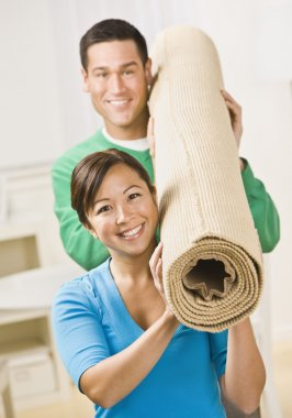 Happy Couple Carrying Carpet Roll