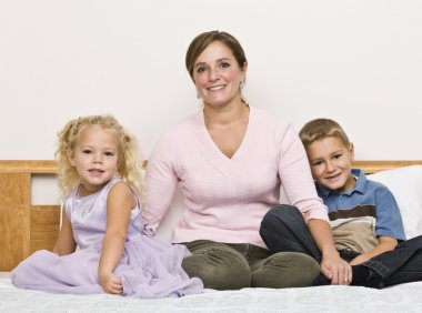 Mother and Children Sitting on Bed