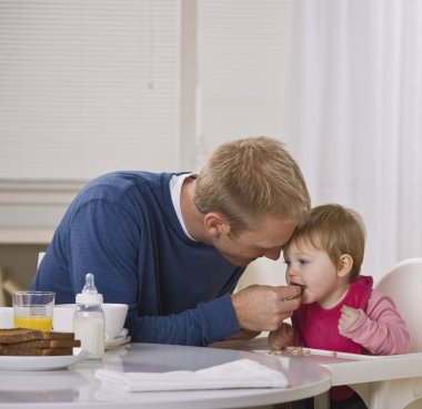 Father Feeding Daughter Breakfast