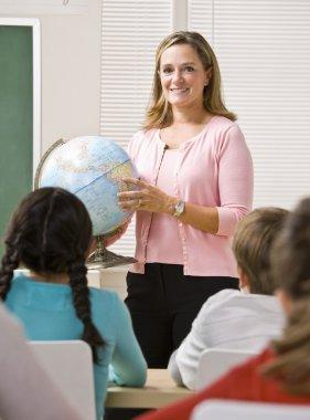 Teacher explaining globe to students