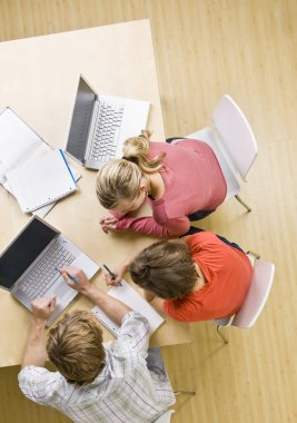 Students studying together in classroom on laptops