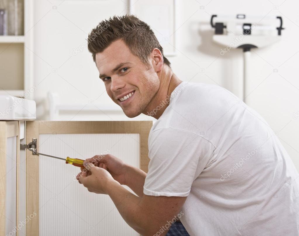 A man is fixing the cabinet door in his bathroom. He is smiling at the camera. Square framed shot.