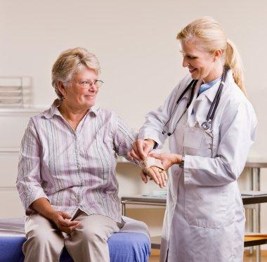 Doctor adjusting senior woman wrist splint