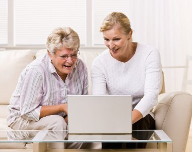 Senior woman and daughter using laptop