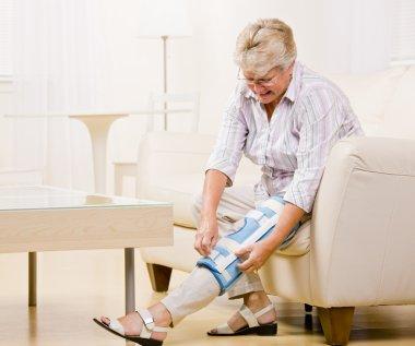 Senior woman adjusting knee brace