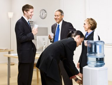 Business drinking water at water cooler