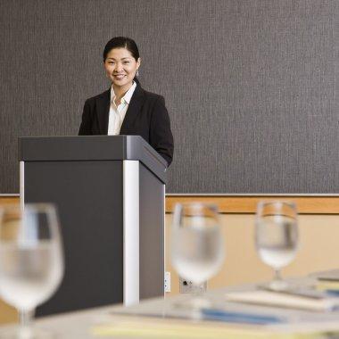 Woman Smiling Behind Podium