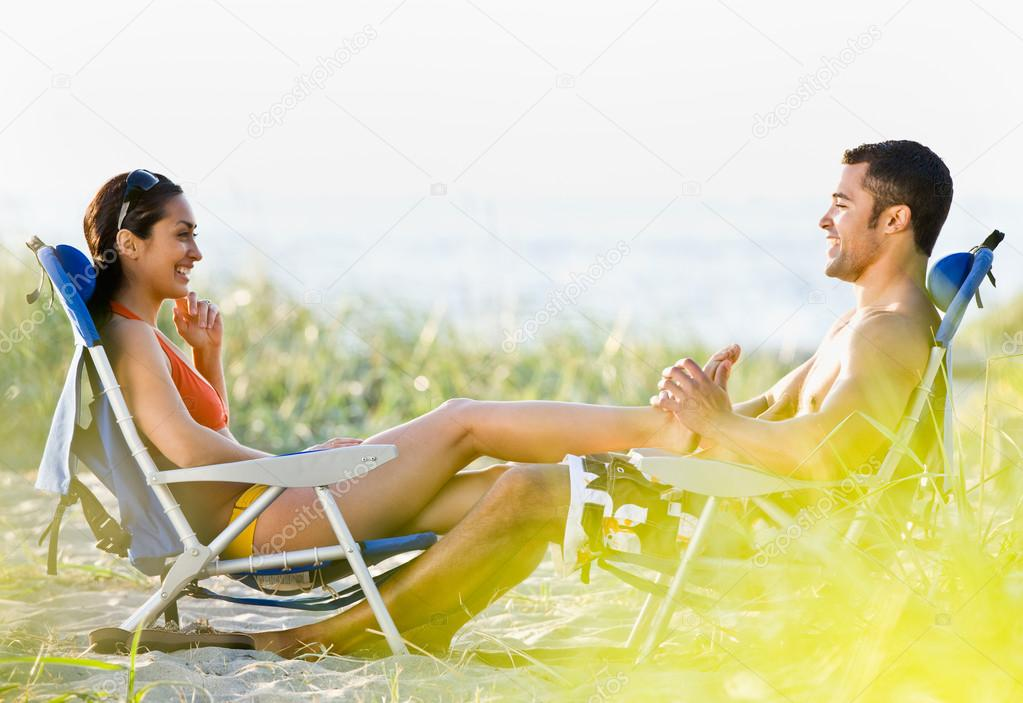 Boyfriend giving girlfriend foot massage at beach
