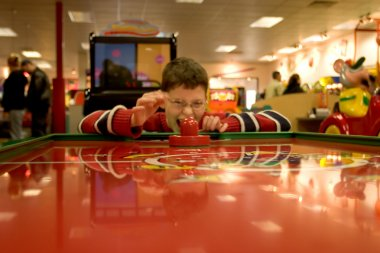 Photo of a silly boy playing air hockey at an arcade stock vector