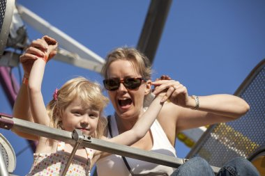 Mother and Daughter on a Ride at the Amusement Park