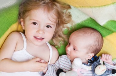 happy little girl with a newborn brother
