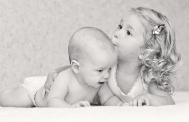 Happy little girl hugging kissing brother