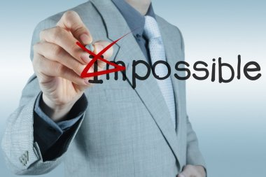 Businessman changing the word impossible into possible