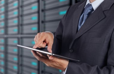 Businessman using tablet computer and server room background