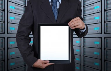 Businessman hand shows blank tablet computer and server room bac