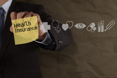 Businessman hand draws health insurance with sticky note and med