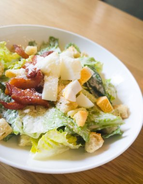 caesar salad placed on top of a wooden table