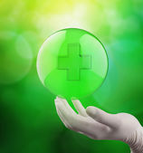 Medizinische Hand mit Globus Select auf dem Erste-Hilfe-Schild