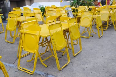 Yellow steel table sets with folding chairs.