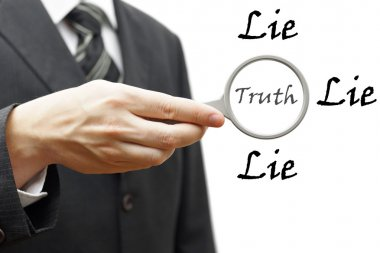 truth and lie concept with businessman holding magnifying glass
