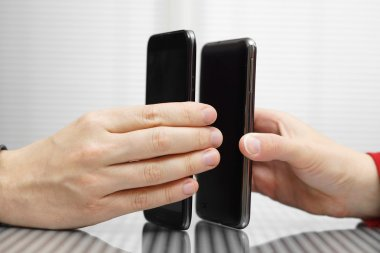 Two hands holding mobile smart phones while transferring data