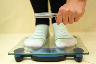 Woman feet on weighing scales looking weight over magnifying gla
