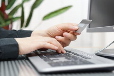 Man is using credit card and computer for  on line payment. inte