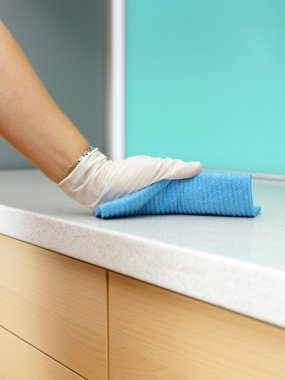 Woman Wearing Apron Cleaning Kitchen worktop