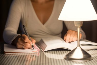 woman is studying and take notes late at night