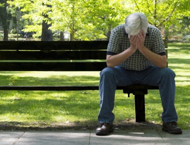 Depressed Older Man On Bench With Focus On Foreground
