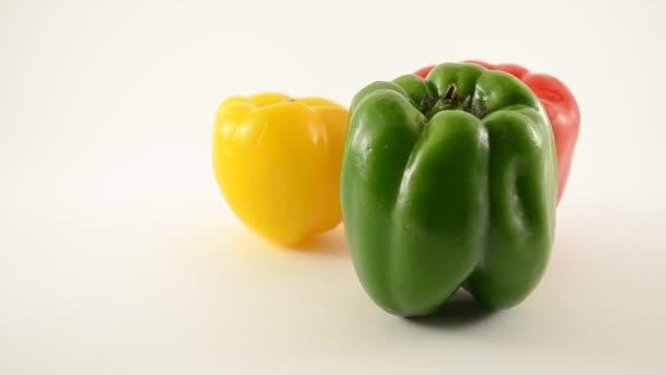 zelený, žlutý a červený pepř proti bílé - trojúhelník uspořádání - dolly vlevo