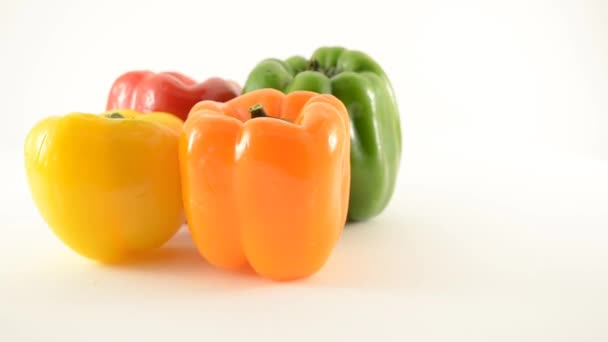 Rotating Orange, Yellow, Green and Red Peppers Against White - Loopable - Locked Off